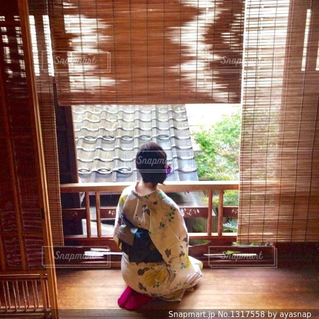 小さな子供は窓の前で座っています。の写真・画像素材[1317558]