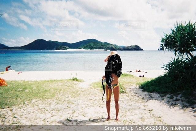水の体の横にある砂浜に立っている人の写真・画像素材[865218]