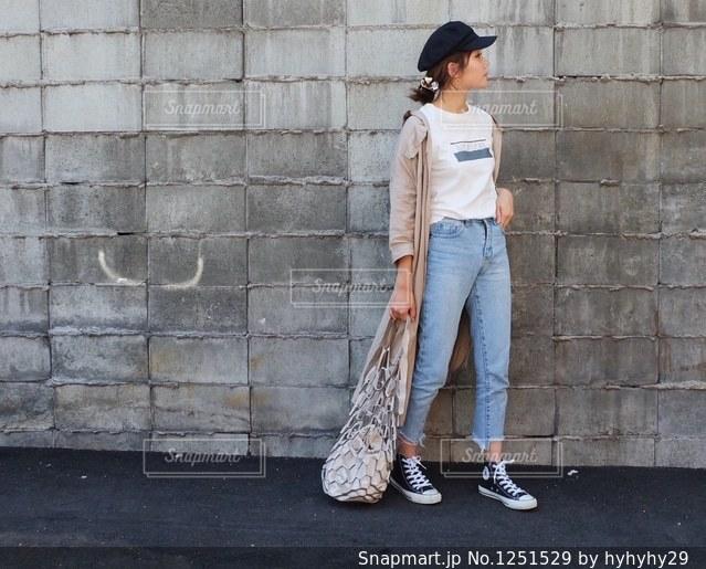 レンガ壁の前に立っている人の写真・画像素材[1251529]