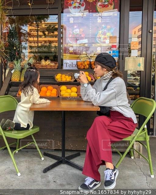 店の前の椅子に座る人の写真・画像素材[1657834]