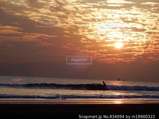 夕日とサーファーと烏帽子岩の写真・画像素材[834094]