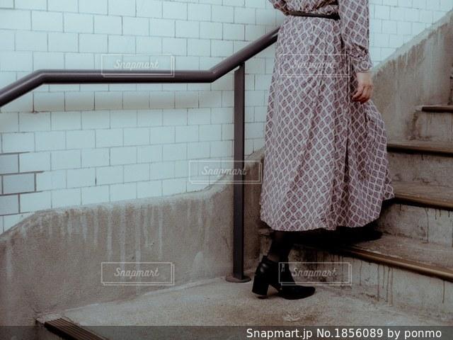タイル張りの壁の前に立っている人の写真・画像素材[1856089]