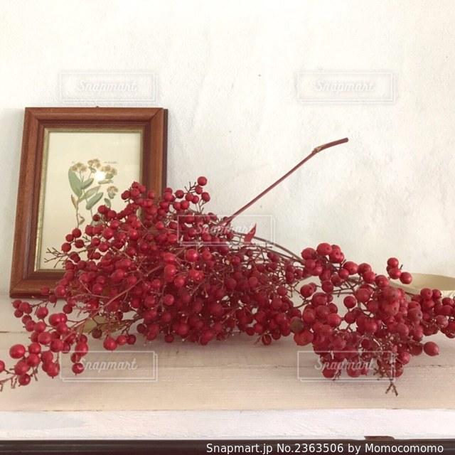 テーブルの上の花瓶の中の赤い花の写真・画像素材[2363506]