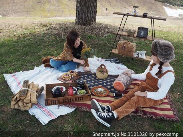 ピクニック用のテーブルに座っている少女の写真・画像素材[1101328]