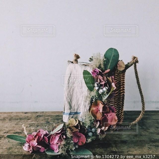 花の花瓶とテーブルに座っている人々 のグループの写真・画像素材[1304272]