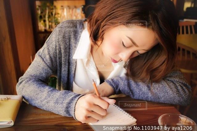 テーブルに座ってメモを取っている女性の写真・画像素材[1103947]