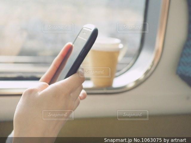 移動中の電車でスマホいじりの写真・画像素材[1063075]