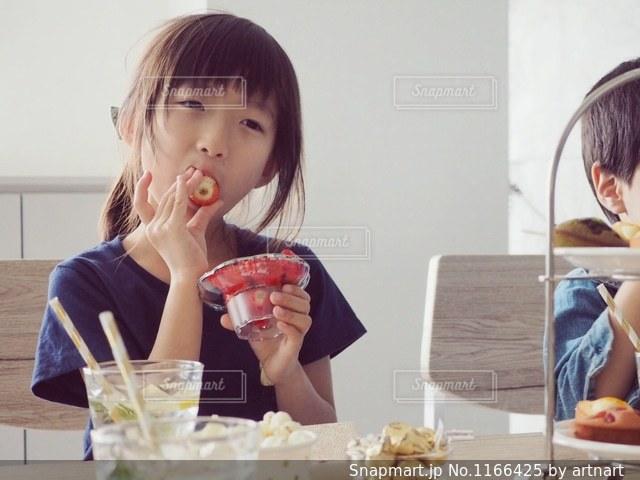いちごを頬張る女の子の写真・画像素材[1166425]