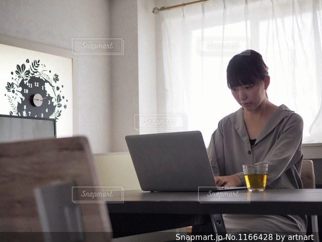ラップトップを使用してテーブルに座っている女性の写真・画像素材[1166428]