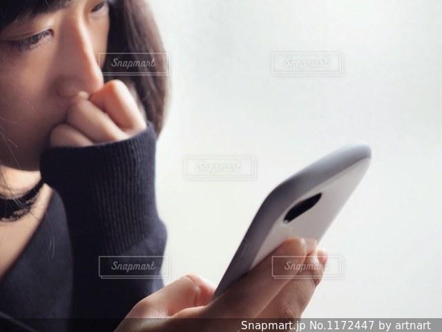 考えながらスマホいじりする女性の写真・画像素材[1172447]