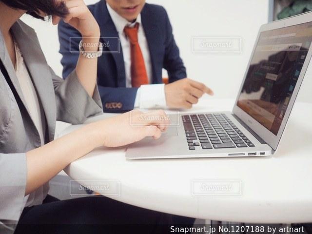 ラップトップ コンピューターを使用して相談している男女の写真・画像素材[1207188]