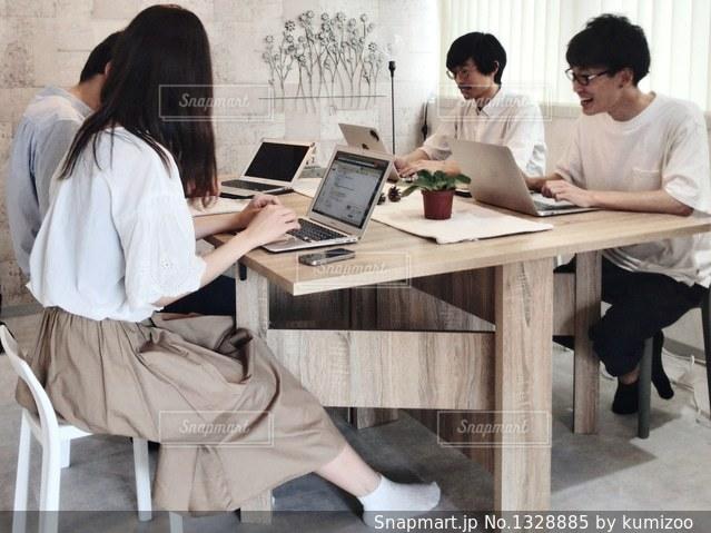 ノート パソコンでテーブルに座っている人々 のグループの写真・画像素材[1328885]