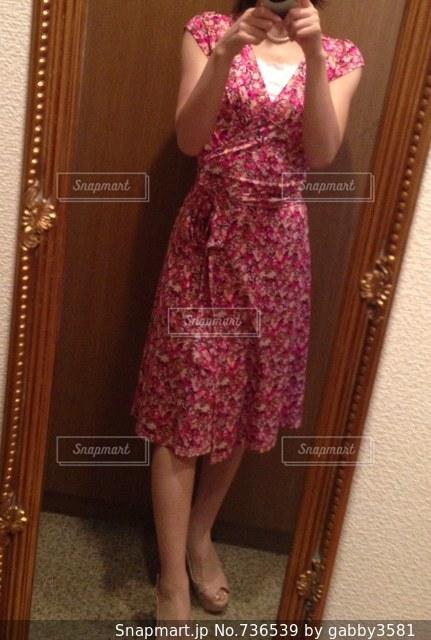 鏡の前のピンクのワンピースをきた女性の写真・画像素材[736539]