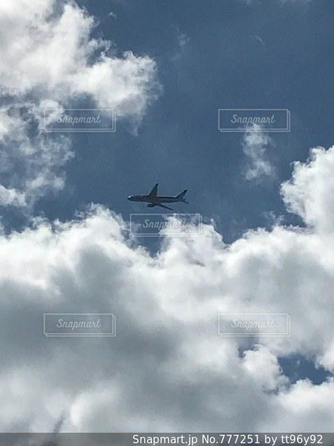 曇りの青い空を飛んでいるジェット大型旅客機の写真・画像素材[777251]