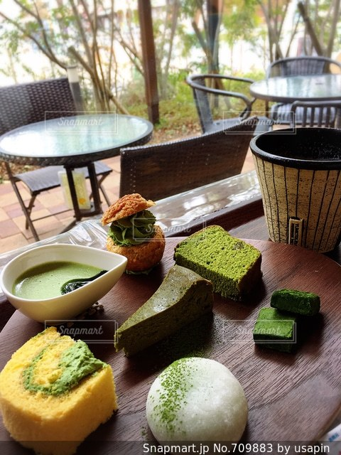 食品のプレートをのせた木製テーブルの上のコーヒー カップの写真・画像素材[709883]