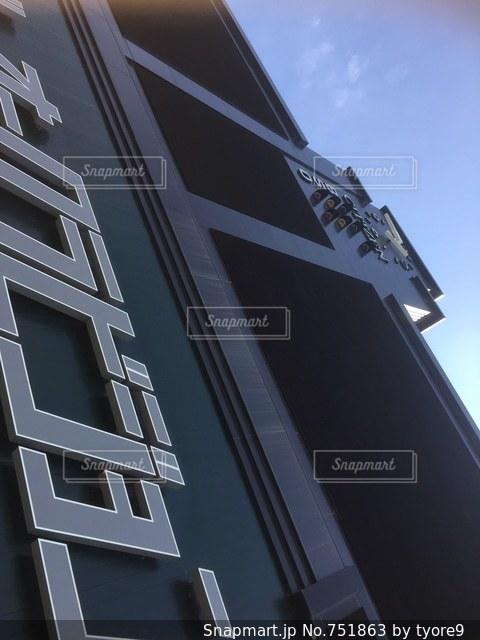 近くに建物の側面から掛かる道路標識のアップの写真・画像素材[751863]