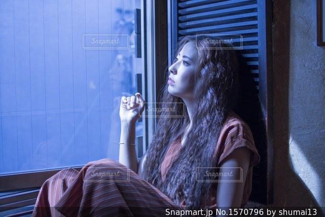 窓辺でくつろぐ素敵な女性の写真・画像素材[1570796]