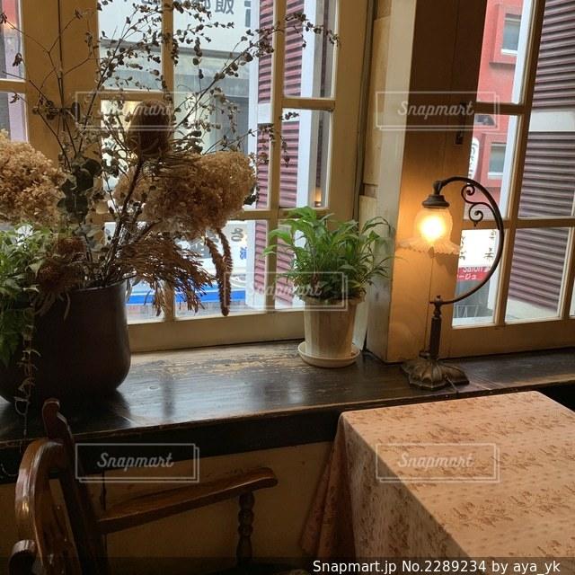 窓の横のテーブルの上の花瓶の写真・画像素材[2289234]