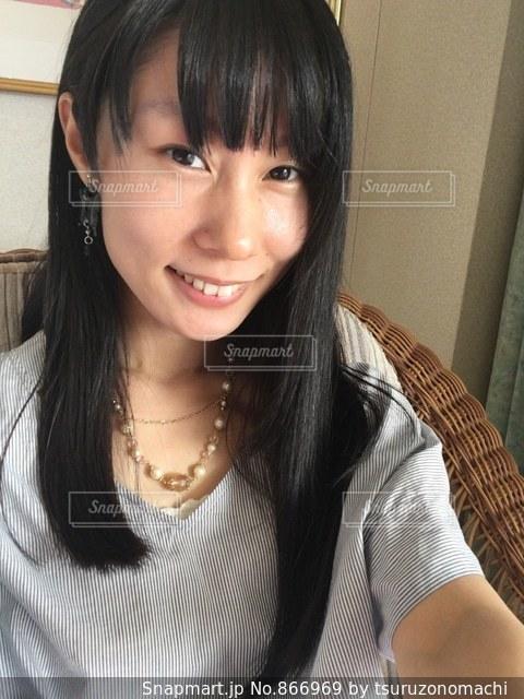 笑顔で籐の椅子に腰掛ける夏服の女性の写真・画像素材[866969]