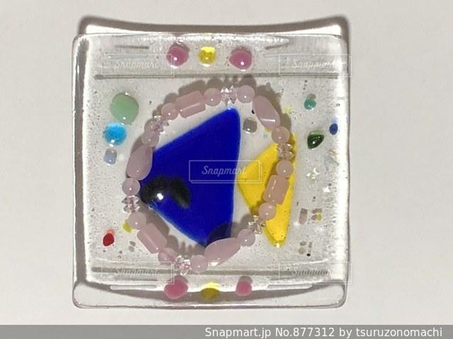 魚の模様のガラス皿にのったローズクォーツのブレスレットの写真・画像素材[877312]