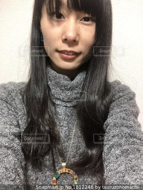 青いピアスをした女性の顔のアップ(2)の写真・画像素材[1012246]