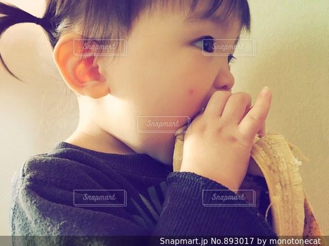 バナナを食べる少年の写真・画像素材[893017]