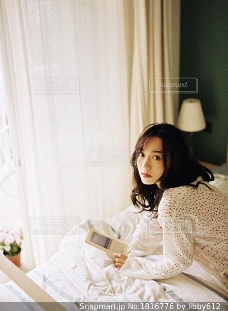 ベッドの上に座っている女性の写真・画像素材[1816776]