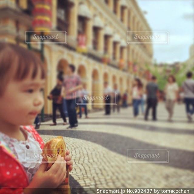 マカオでエッグタルトを食べる女の子の写真・画像素材[902437]