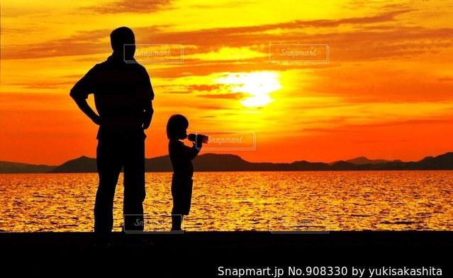 日没の前に立っている男の写真・画像素材[908330]