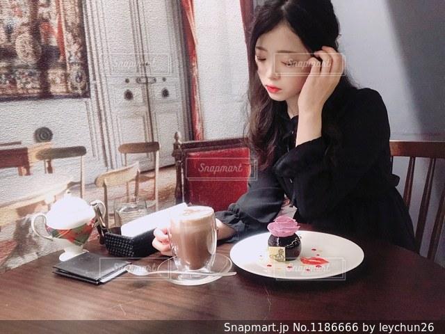 食事のテーブルに座っている女性の写真・画像素材[1186666]