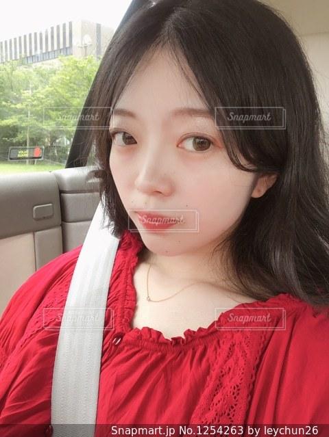 近くに赤いシャツの女性のアップの写真・画像素材[1254263]