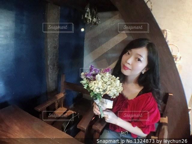 花の花瓶とテーブルに座っている女性の写真・画像素材[1324873]