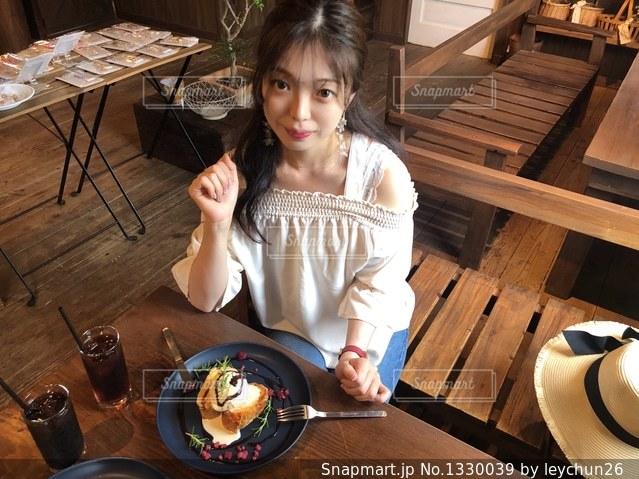 食品のプレートをテーブルに座っている少女の写真・画像素材[1330039]