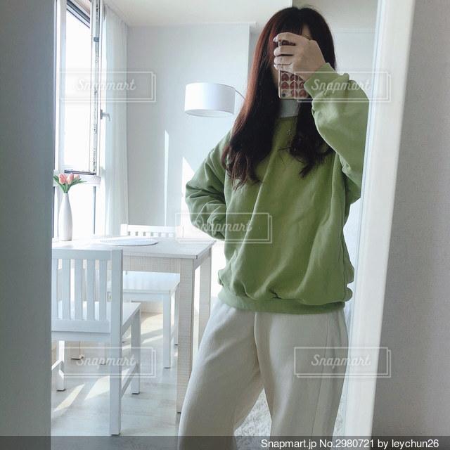 カメラに向かってポーズをとる鏡の前に立っている女性の写真・画像素材[2980721]