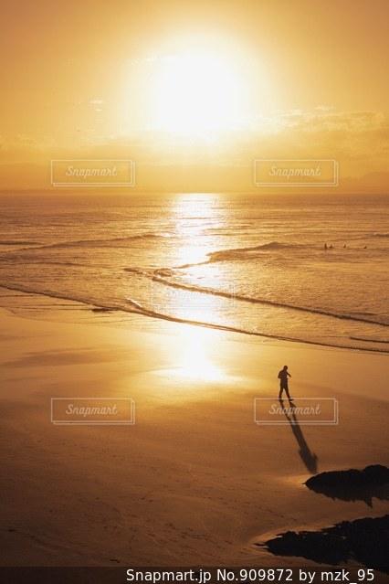 海の横にある砂浜のビーチに沈む夕日の写真・画像素材[909872]