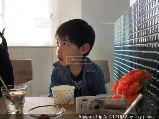 窓の前のテーブルに座っている男の子の写真・画像素材[1171832]