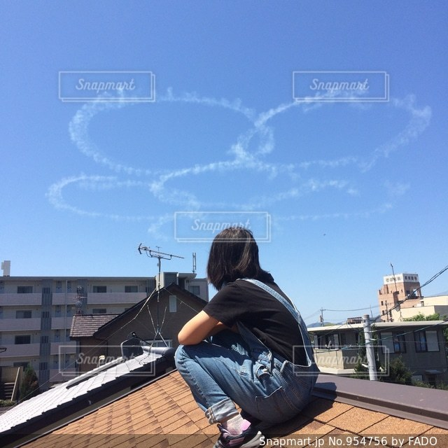 屋根の上から空を見上げる少女の写真・画像素材[954756]