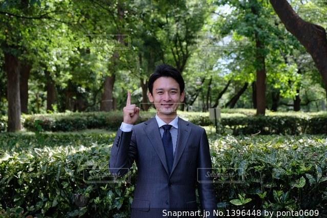 身に着けているスーツとネクタイの森の隣に立っている男の写真・画像素材[1396448]