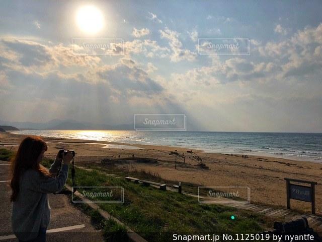 神々しい夕日と女性の写真・画像素材[1125019]