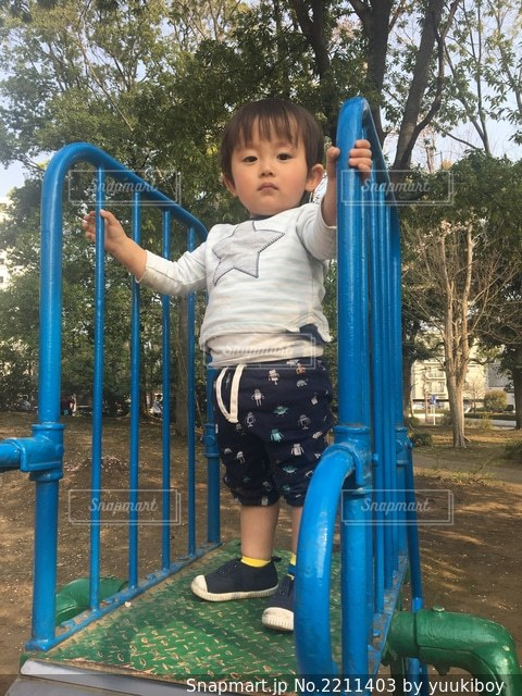 公園の滑り台の上に立っている少年ゆうきボーイ。の写真・画像素材[2211403]