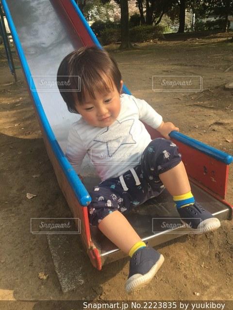 公園の滑り台に座っている小さな男の子ゆうきボーイ。の写真・画像素材[2223835]