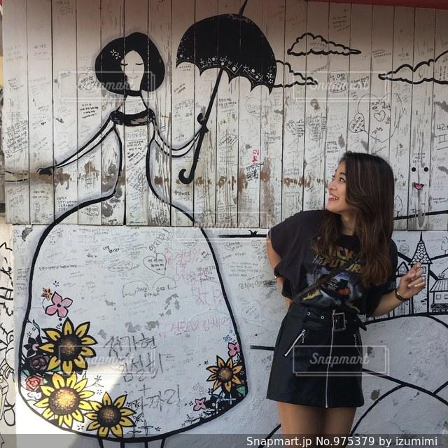 覆われている落書きの壁の横に立っている女性の写真・画像素材[975379]
