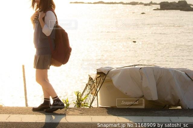 海辺の道をやや寂しそうに歩くJKの写真・画像素材[1168909]