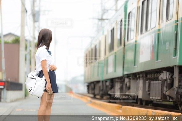 電車の通過待ちをしているJKの写真・画像素材[1209235]