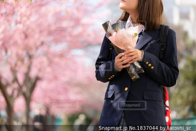 ブーケを持ち、桜の花を見やる女子高生の写真・画像素材[1837044]