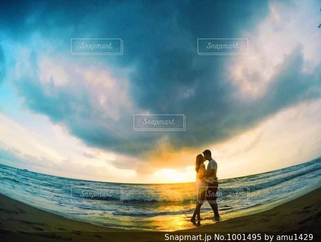海の横にあるビーチの上を歩く男の写真・画像素材[1001495]
