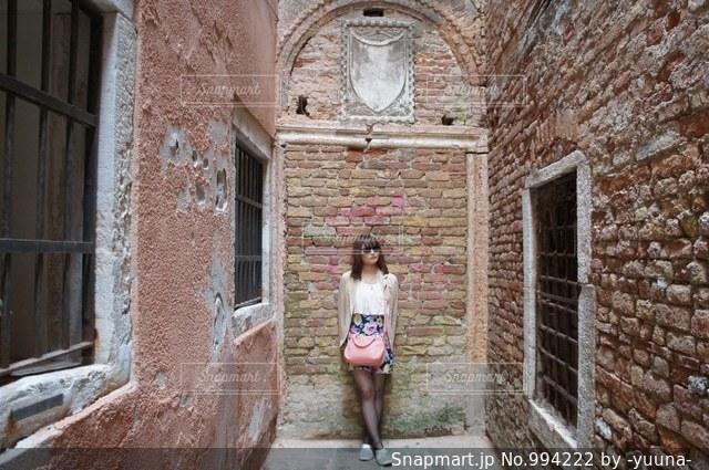 れんが造りの建物の前に立っている女性の写真・画像素材