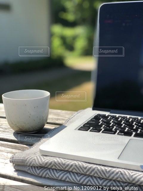 コーヒー片手に外で仕事の写真・画像素材[1209012]