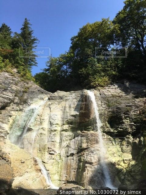 岩の横にある大きな滝の写真・画像素材[1030072]