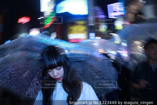 人が傘を持って雨の中を歩いての写真・画像素材[1223449]